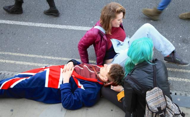 Fulde studerende, der tager sig en lur på fortorvskanten.